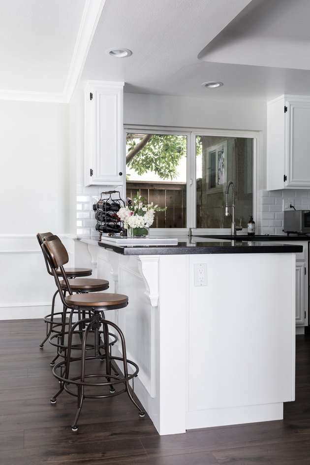 Dark wood kitchen flooring idea with wood and metal bar stools and black countertop