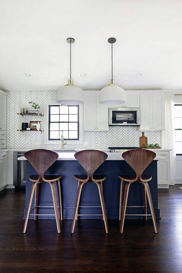 Dark wood kitchen flooring idea with blue island and modern pendant lights