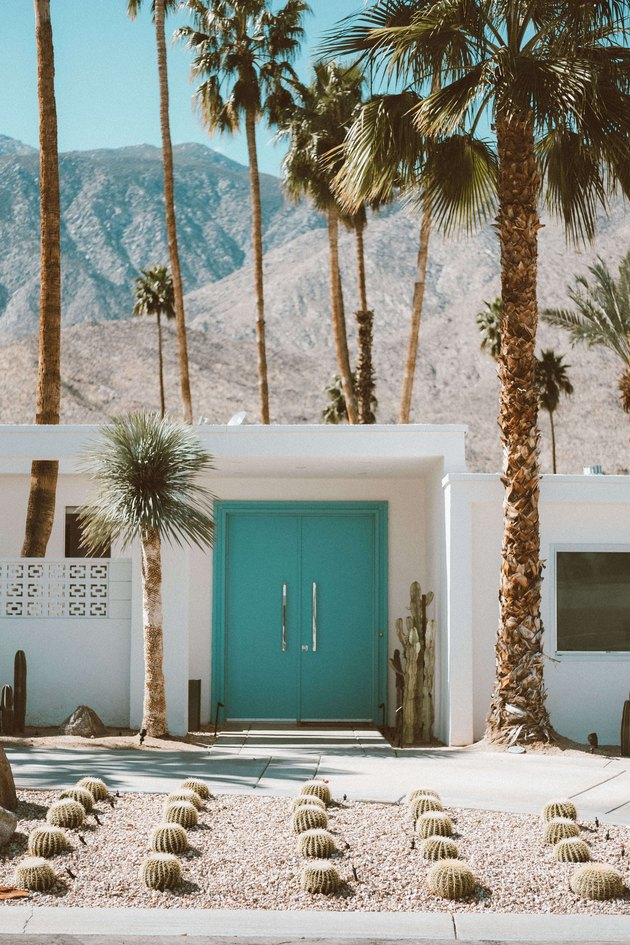 Desert style home in Palm Springs, California with palm trees and turquoise front door