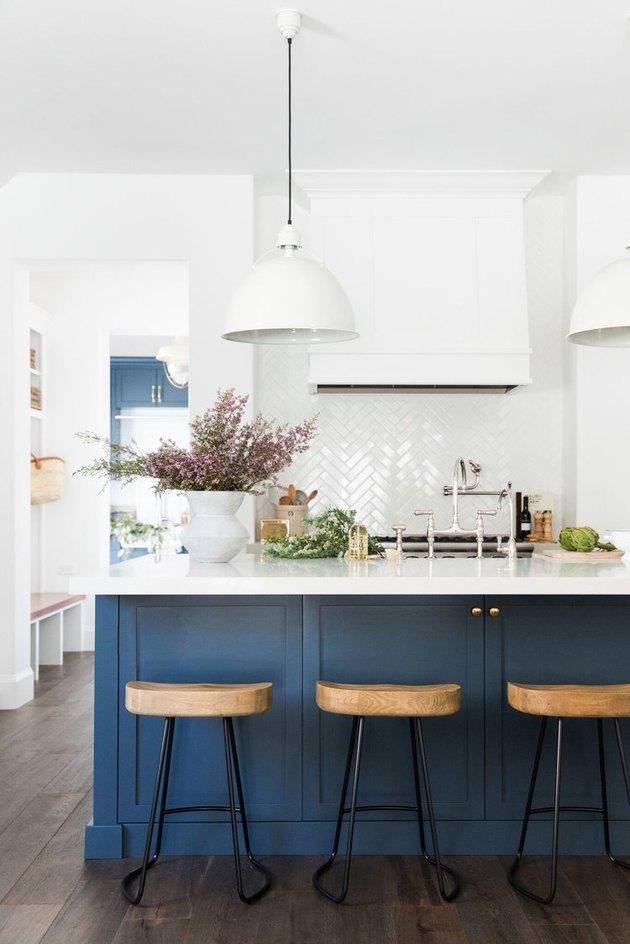 Dark wood kitchen flooring idea with blue island and herringbone white tile backsplash