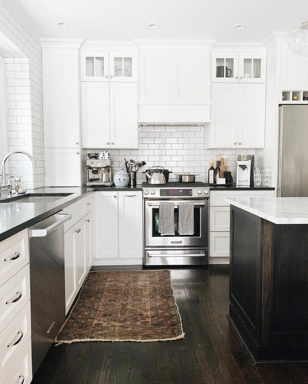 white kitchen dark floors with black countertops and dark hardwood floors