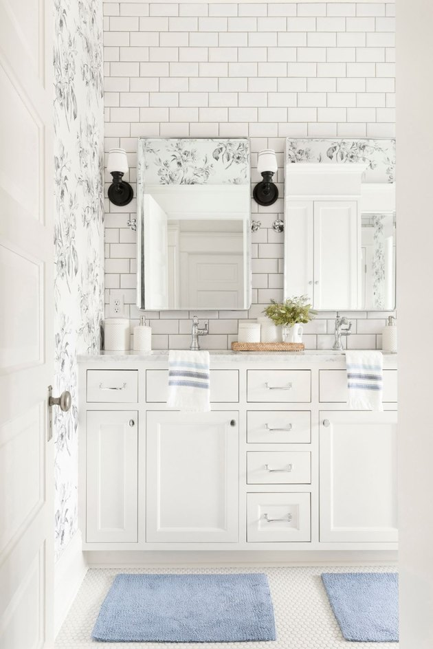 Double bathroom vanity with white cabinets and floral wallpaper