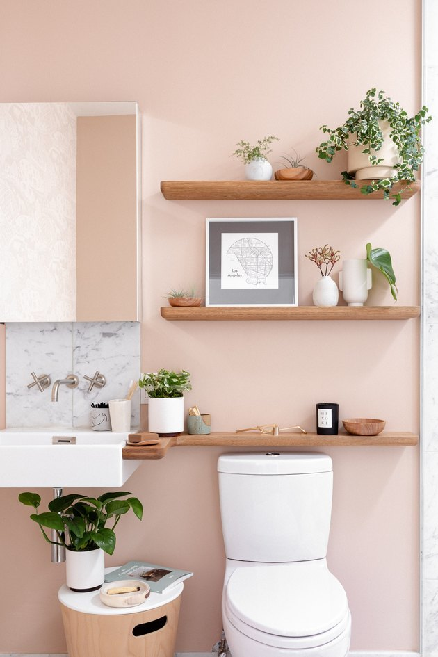 bathroom with millennial pink wall and wood shelves with plants and framed artwork