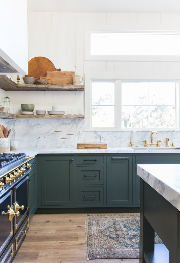 green kitchen cabinets with marble countertop and backsplash