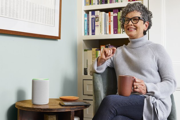 woman sitting with mug near Amazon Echo