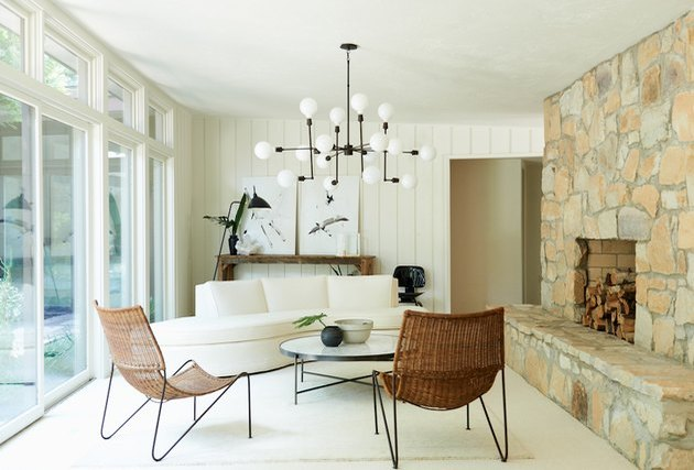 neutral living room with rock fireplace and modern chandelier