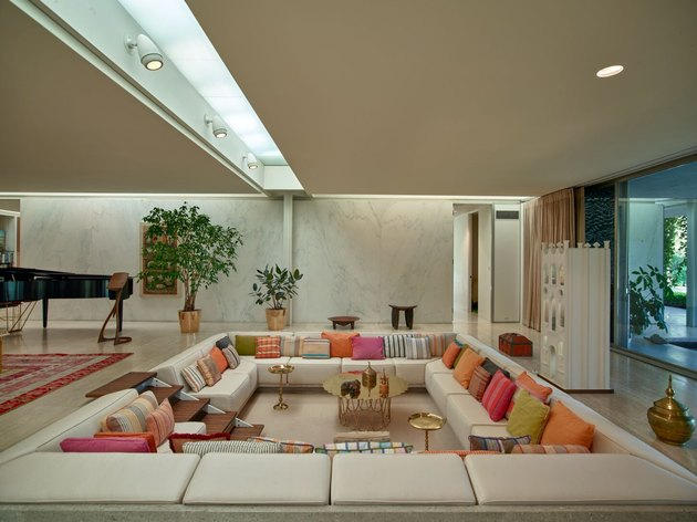 a conversation pit featuring a small wooden staircase in wraparound couch with multicolored pillows