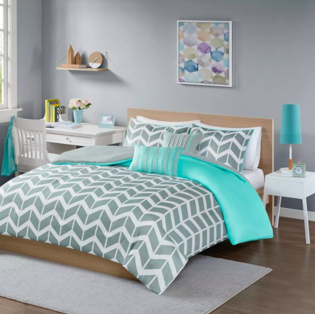 bed with chevron pattern bedding, night stand and desk nearby
