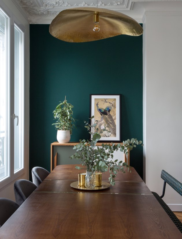 green dining room in Paris apartment with mismatched chairs and modern chandelier