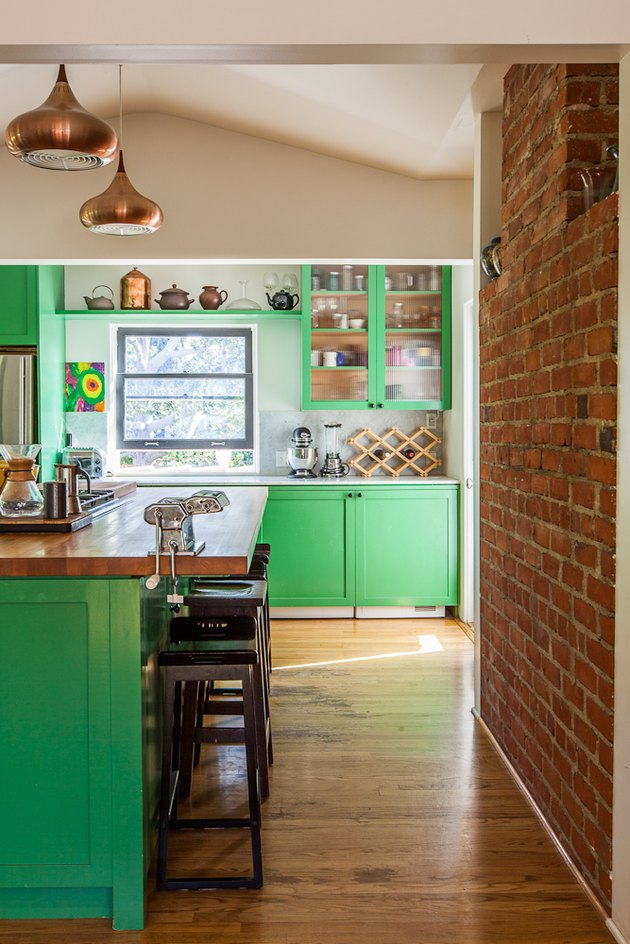neon green cabinets in kitchen with brick accent wall