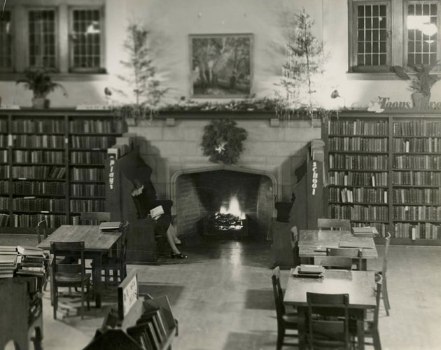 a library featuring an inglenook at Christmas surrounded by two benches and a woman reading a book