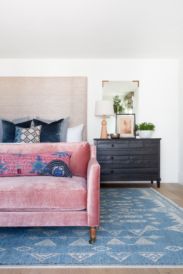 A pink velvet couch in the master bedroom