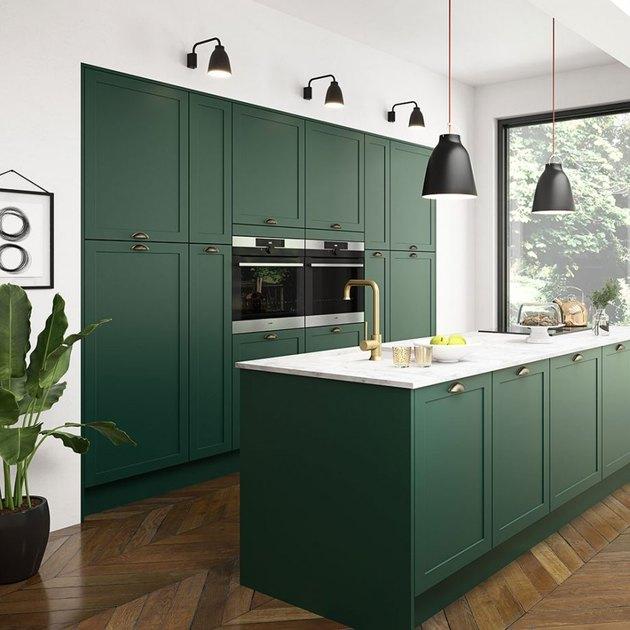 dark green modern kitchen with black light fixtures and herringbone wood flooring