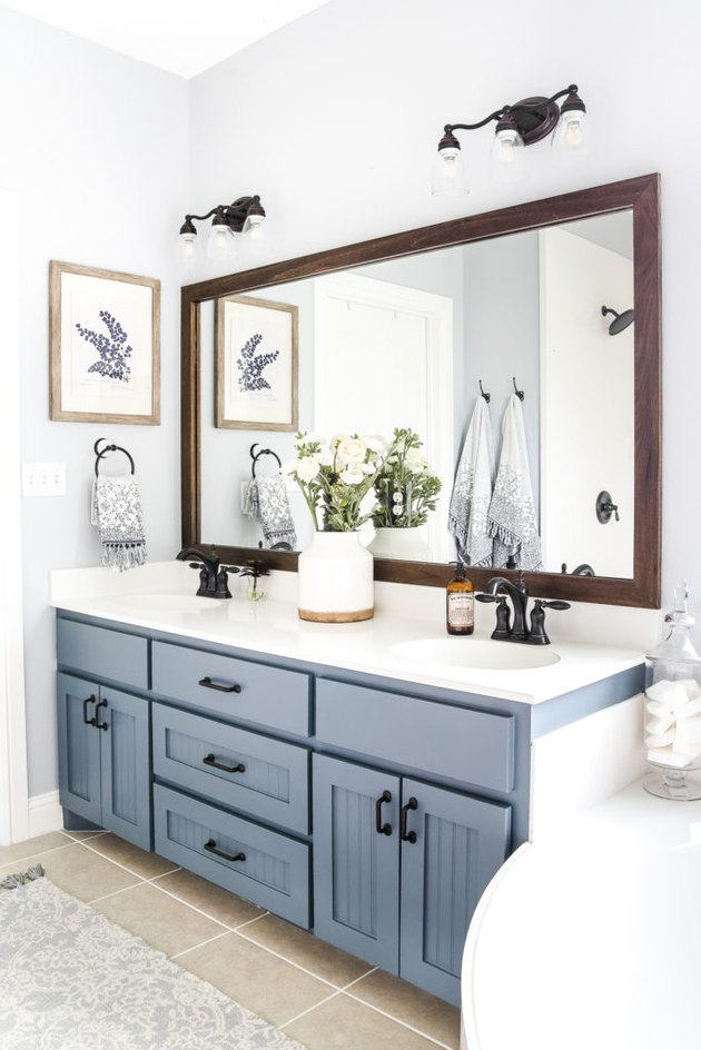 Double bathroom vanity with blue cabinets and large mirror