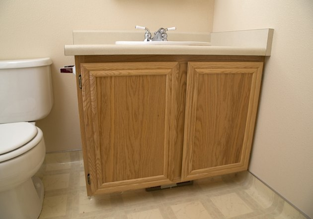 Painted bathroom cabinets before and after featuring oak cabinets