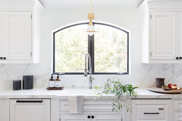 An all-white kitchen with marble counters and backsplash