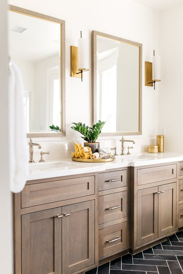 Double bathroom vanity with wood cabinets and wall sconces
