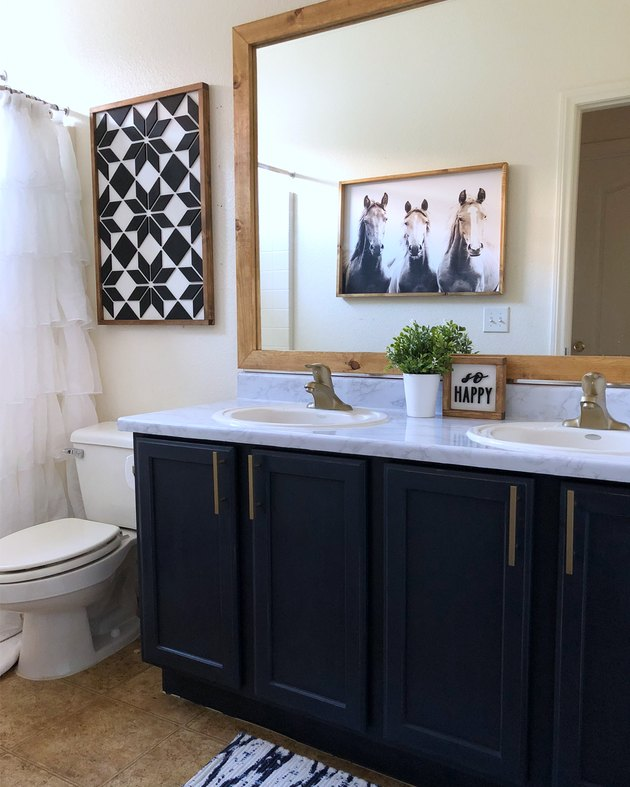 Painted bathroom cabinets before and after featuring navy cabinets and farmhouse decor