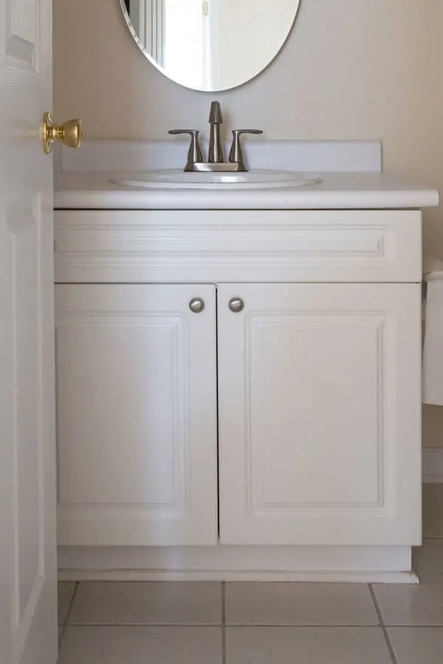 Painted bathroom cabinets before and after featuring white vanity