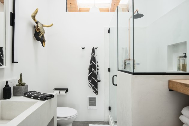 Desert-style white bathroom with skull on wall and black and white towels