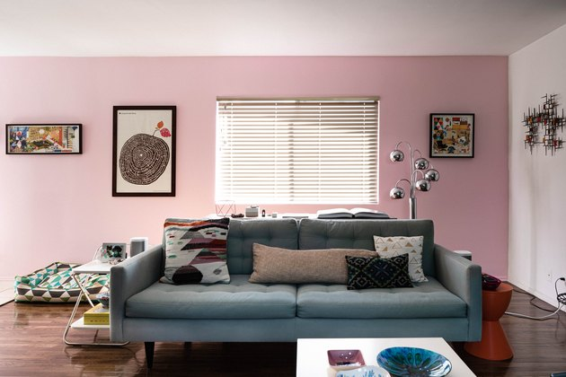 living room space with pink wall and blue couch and framed artworks on the wall