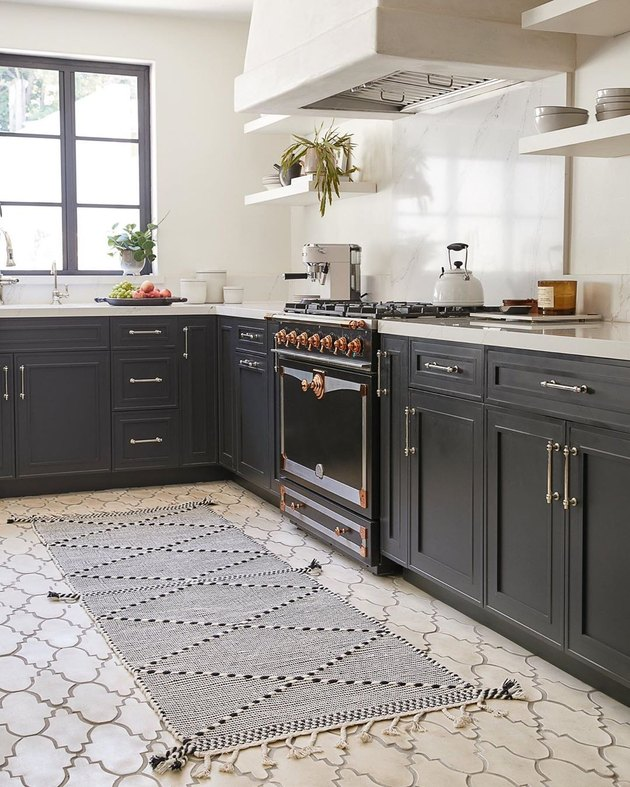 kitchen space with dark cabinets, patterned rug, and cream colored floor