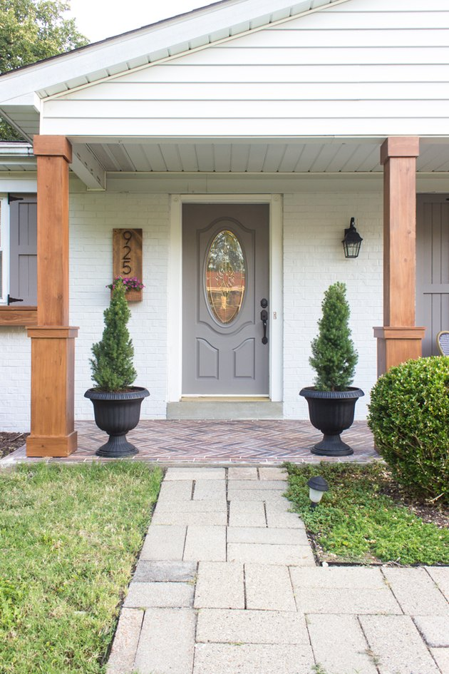 Craftsman front porch with matching wood columns and topiaries