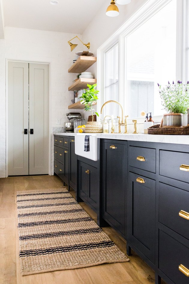 striped jute rug for kitchen floor with navy cabinets and brass fixtures