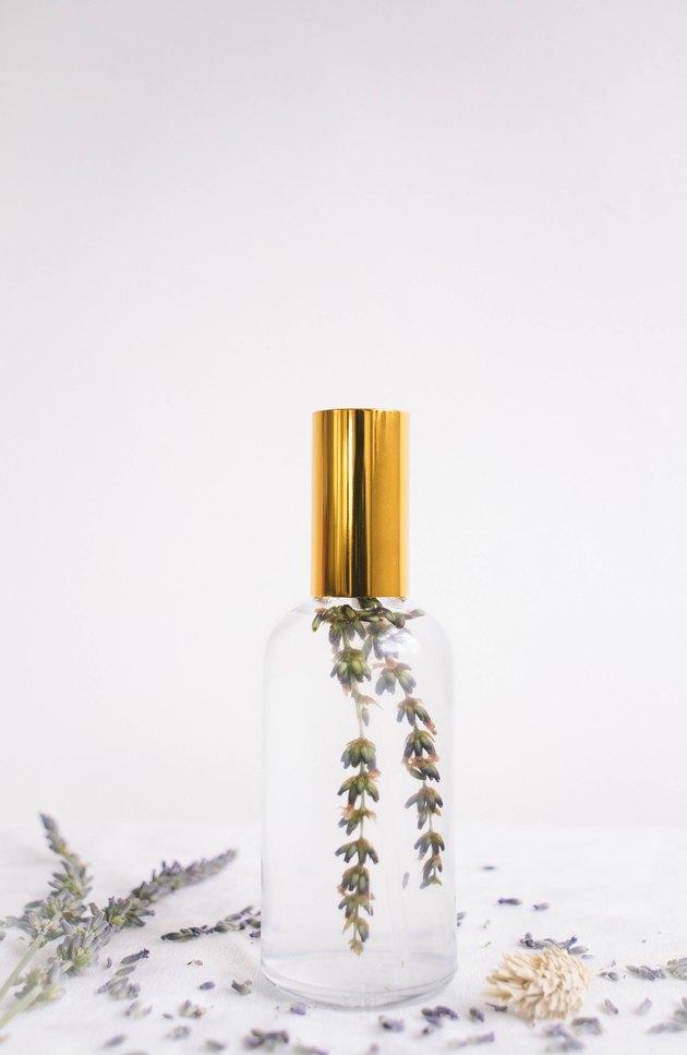 Brume d'oreiller bricolage dans une bouteille en verre avec dessus en or et brin de lavande à l'intérieur