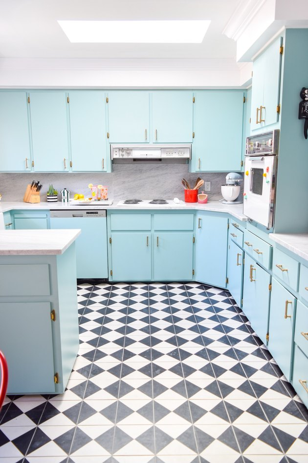 kitchen space with light blue cabinets and black and white patterned flooring