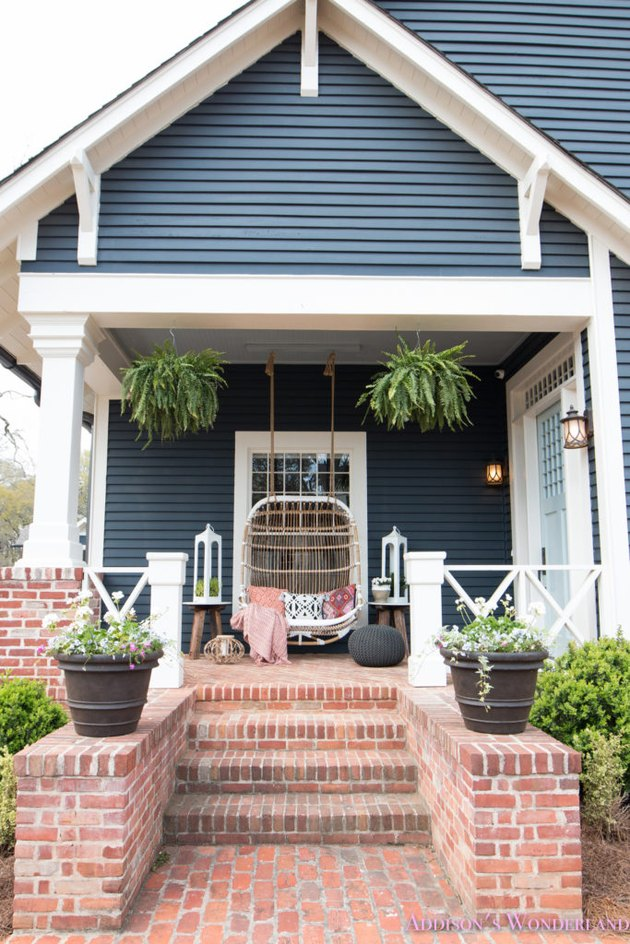 Craftsman front porch with hanging rattan chair and white lanterns