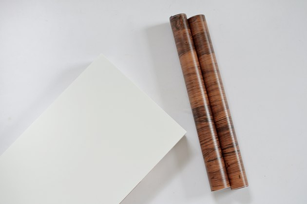 white ikea shelf and roll of walnut contact paper
