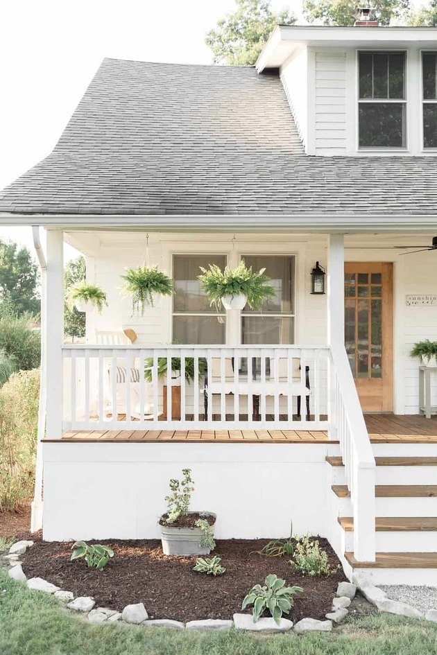 Craftsman front porch with farmhouse details and hanging ferns