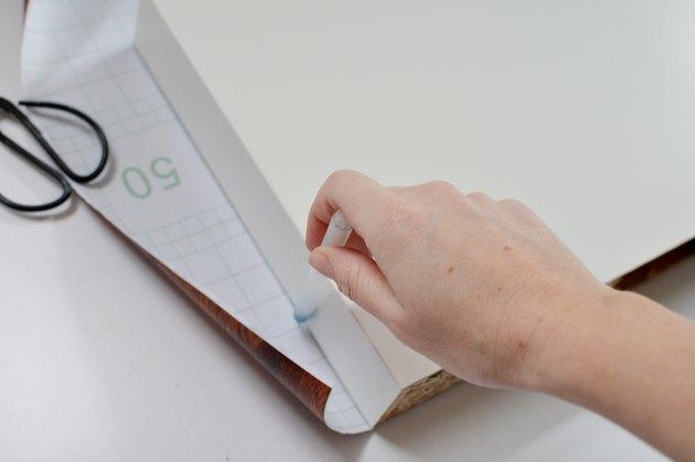 hand holding pen marking outline of shelf