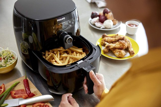 Black air fryer with fries in basket