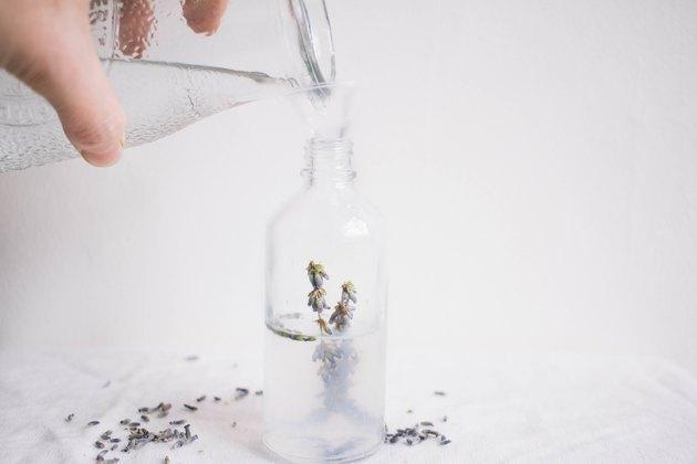 Verser de l'eau distillée dans une bouteille en verre avec de la lavande à l'intérieur