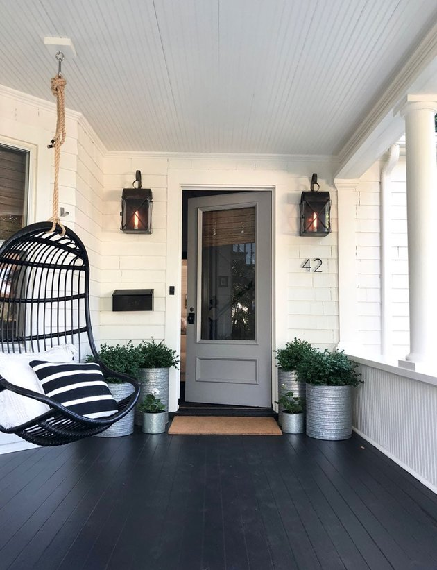 Craftsman front porch with hanging black chair and black lantern wall sconces