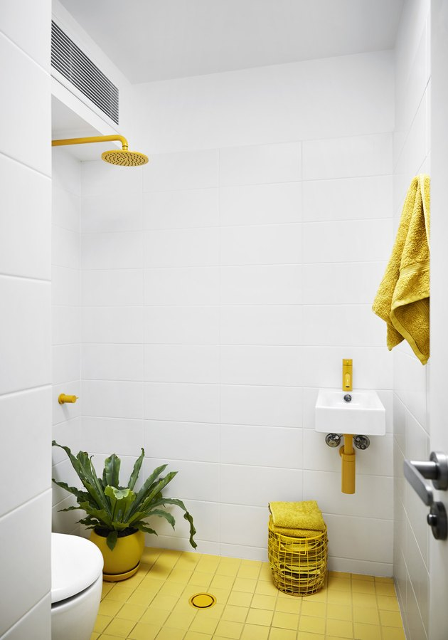 white tiled bathroom with yellow floor and yellow fittings