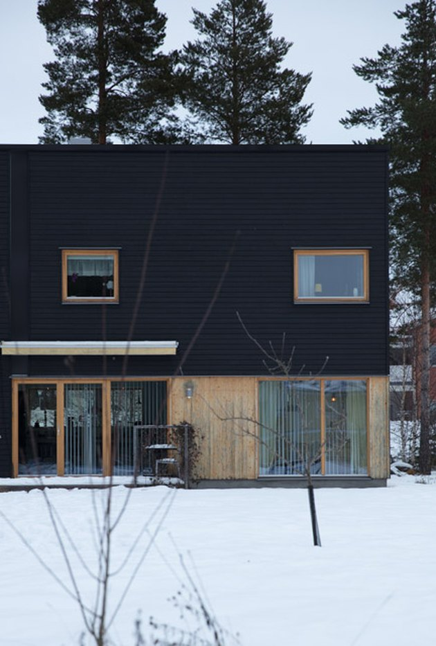 Scandinavian style black house with natural wood in snowy natural area