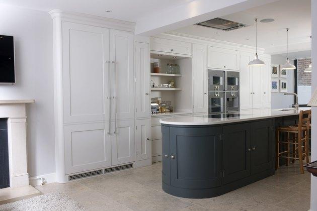 white kitchen with curved green kitchen island