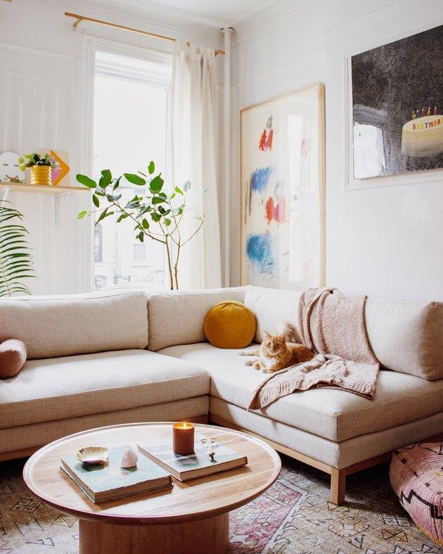 minimal white Scandinavian boho living room with taupe and wood sofa