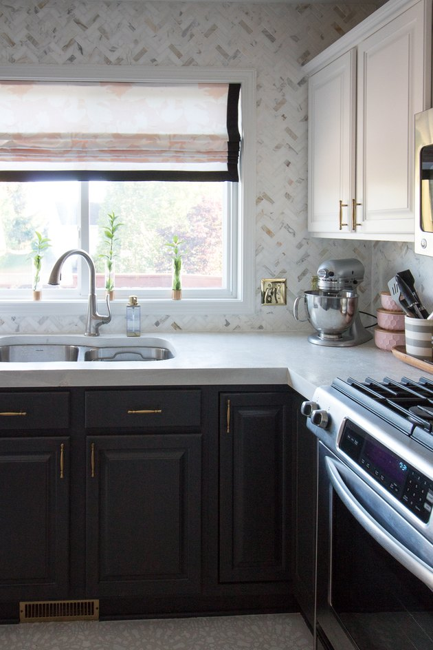 Marble tile herringbone backsplash with black cabinets and sink