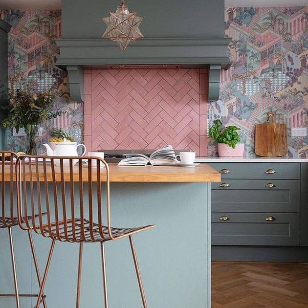 pink pastel herringbone backsplash and muted cabinets with patterned wallpaper