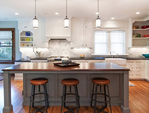 Gray kitchen island with wood countertop and wood bar stools.