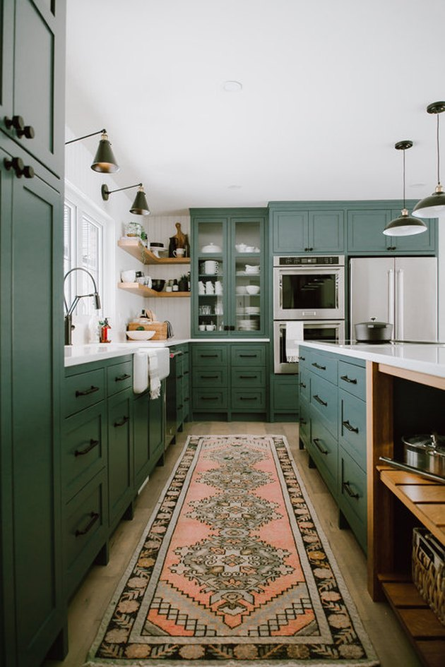 vintage rug for kitchen floor with green cabinets and black fixtures