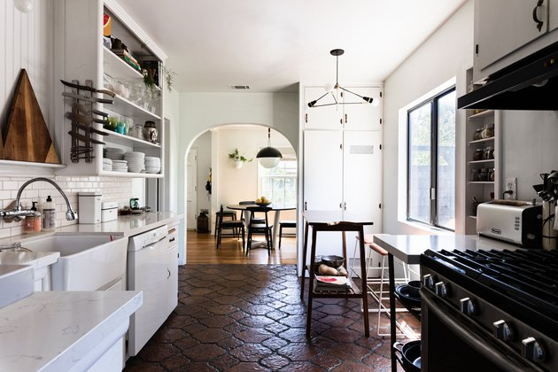 White kitchen cabinets with dark hexagon tile floor and black stove