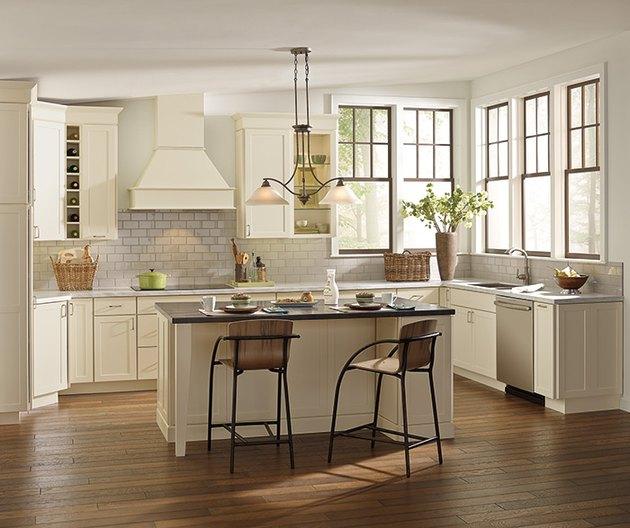 Cheery cream kitchen corner windows, wood floors, rectangular island and barstool seating.