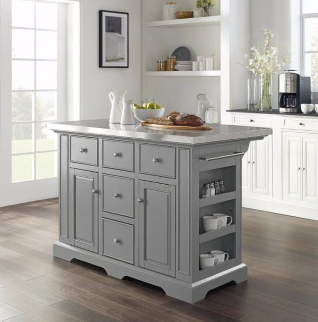 Gray moveable kitchen island in kitchen with white cabinets and wood floors.