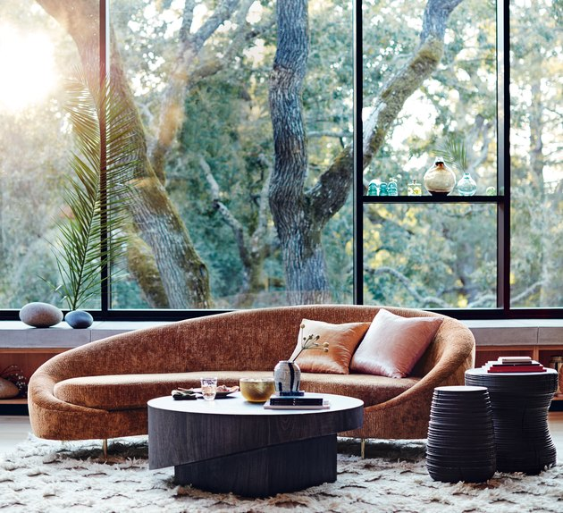 living room with large glass windows and curving velvet couch