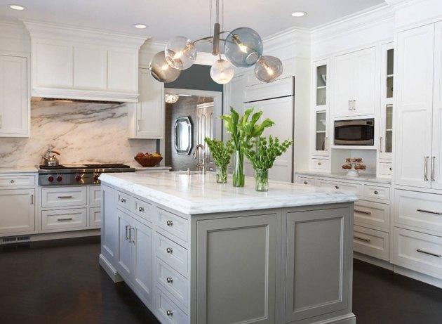 Kitchen with white cabinets, marble backsplash, kitchen island with gray cabinets. Modern glass chandelier.